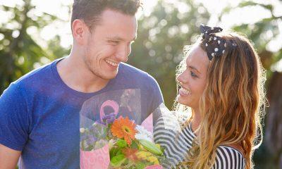 man geeft vrouw bloemen